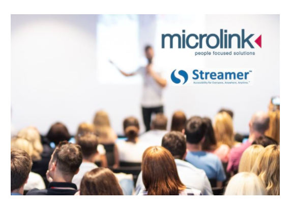 A guy doing a presentation for a groupof people. Microlink and Streamer logo on the top right